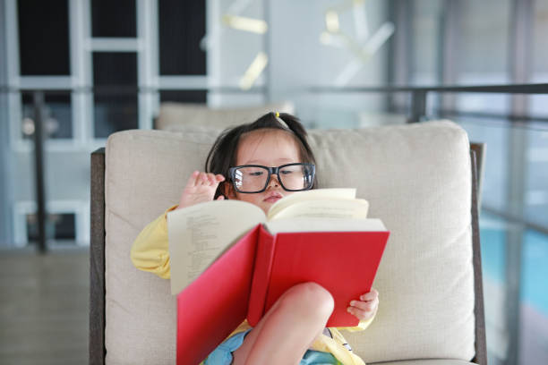 little child girl with glasses reading book in library, education concept. - genius stock photos and pictures