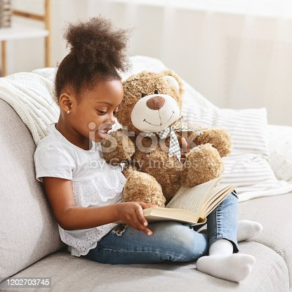 Black little child girl holding teddy bear and reading book, sitting on sofa at home