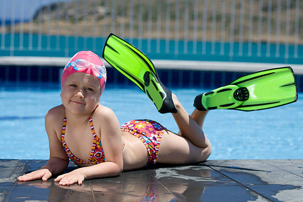 Little child in bathing cap, glasses, fins near swimming pool stock photo