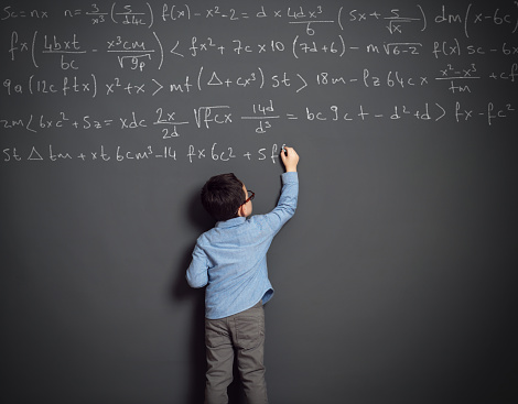 Cute child in front of huge blackboard. He knows answer. He writing formula.