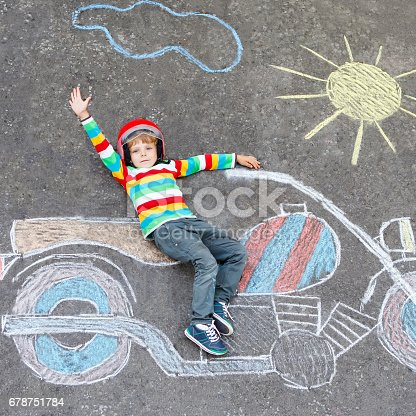 istock Little child in helmet with motorcycle picture drawing with colorful chalks. Children, lifestyle, fun concept. 678751784