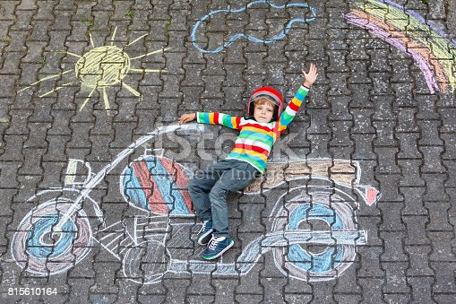 istock Little child in helmet with motorcycle picture drawing with colorful chalks. Children, lifestyle, fun concept. 815610164