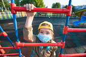 Happy little child in protective mask on a playground during the covid-19 epidemic. New normal.