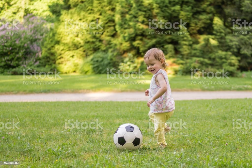 Little child is playing with football ball in park. stock photo