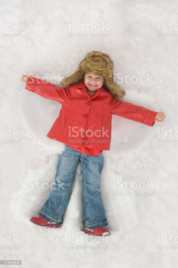Little child making a snow angel stock photo