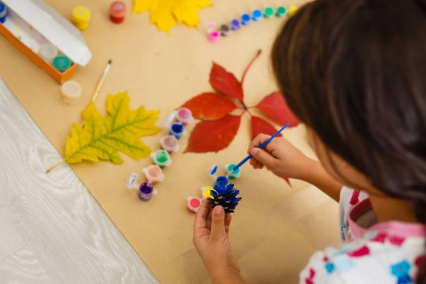 little child making autumn decoration from chestnut, pine cones and acorns stock photo