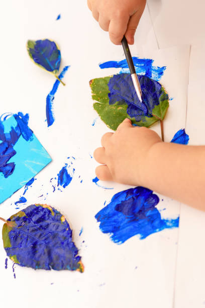 little child painting leaves blue color, crafts. kid stock contributor painting trendy color 2020. - contributor stock pictures, royalty-free photos & images