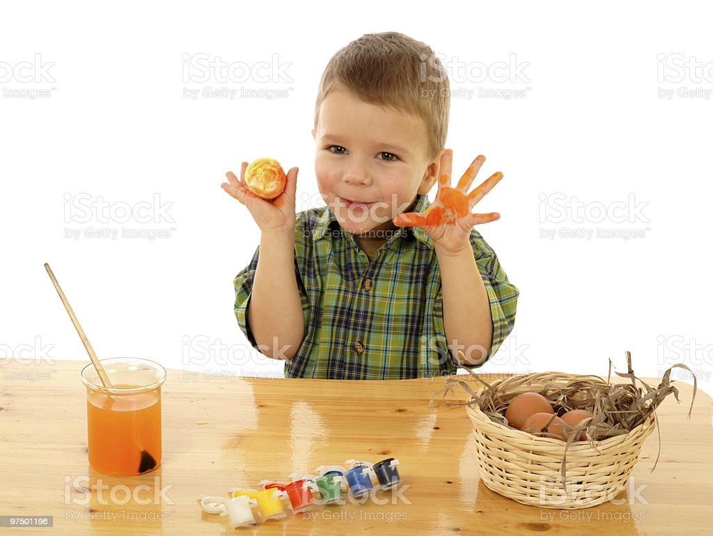 Little child painting the easter eggs and showing dirty hands royalty-free stock photo