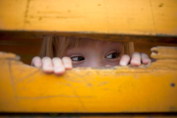Little child peeking at playground Cute little child peeking at playground hide and seek stock pictures, royalty-free photos & images