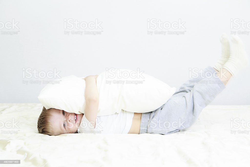 little child playing in bed stock photo