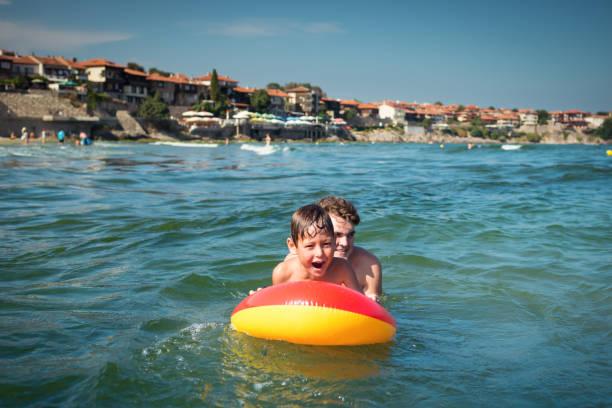 Little child playing in sea on inflatable mattress on waves with and picture id953168484?b=1&k=6&m=953168484&s=612x612&w=0&h=isovofmrbmd6n 6zrosq1sqaxybvchhpxrgaiwtmfai=