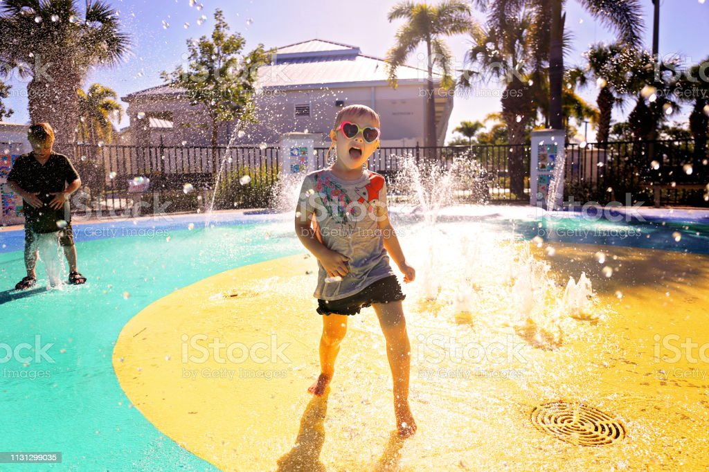 Little Child Playing in Water at Splash Park on Summer Day stock photo