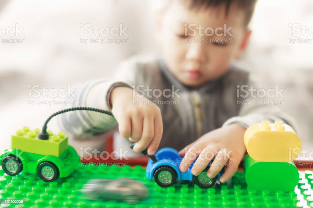 Little child playing with lots of colorful plastic blocks indoor. kid boy having fun with building and creating. Selective focus on toy stock photo