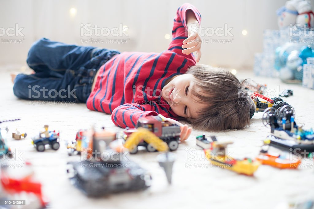 Little child playing with lots of colorful plastic toys indoor stock photo