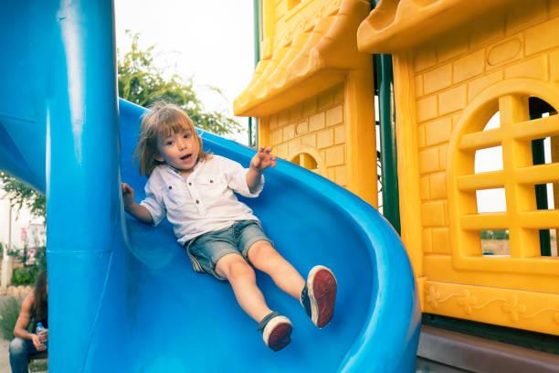 Little child plays on playground slide stock photo