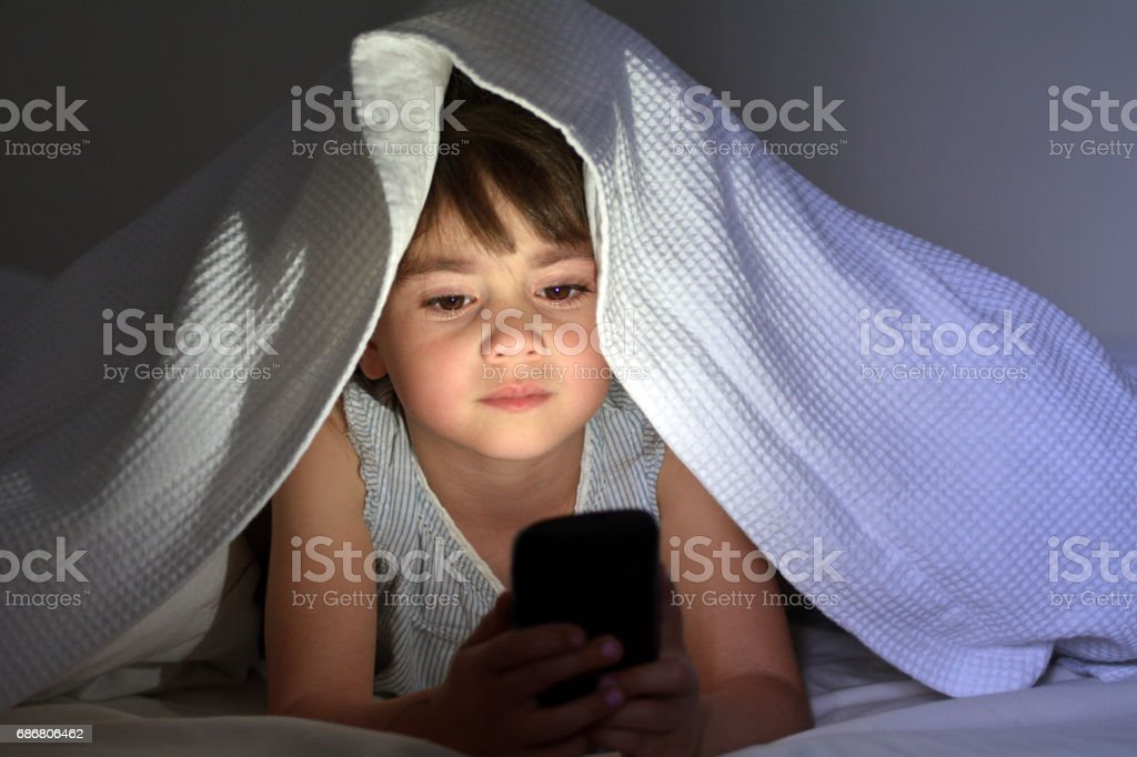 Little child plays on smart phone in bed under the covers at night stock photo