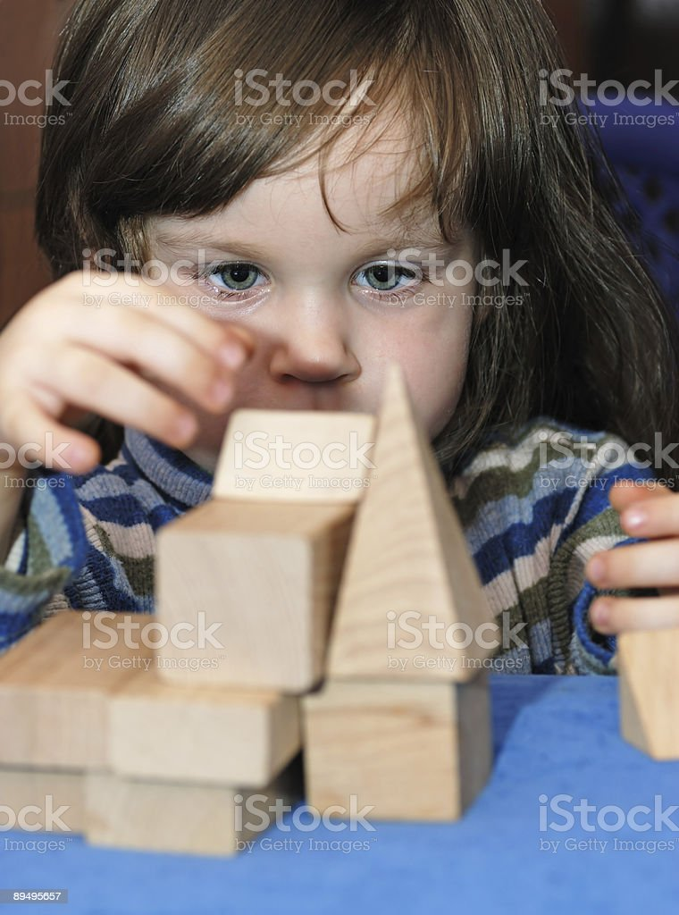 Little child pretending to be an architect with wood blocks royalty free stockfoto