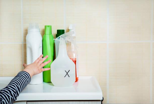 어린 아이가 가정용 화학 물질에 도달 합니다. 어린이에 게 서 멀리 하십시오. 아이 들을 위한 집에서 위험. - 독성 물질 뉴스 사진 이미지