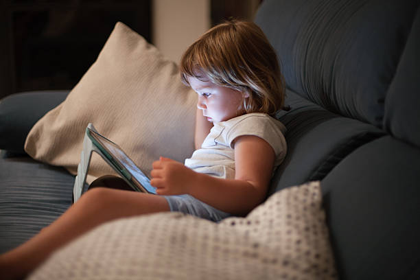 little child sitting comfortably in sofa watching tablet – Foto
