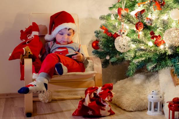 kleines kind sitzt auf sessel und beobachtete handy weihnachtsbaum - kinder weihnachtsfilme stock-fotos und bilder