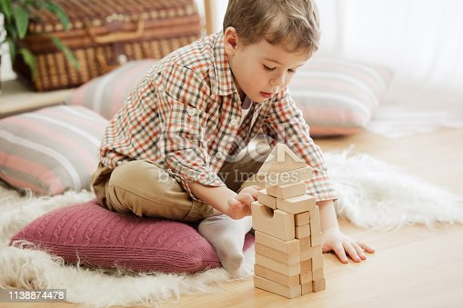 istock Little child sitting on the floor. Pretty boy palying with wooden cubes at home 1138874478