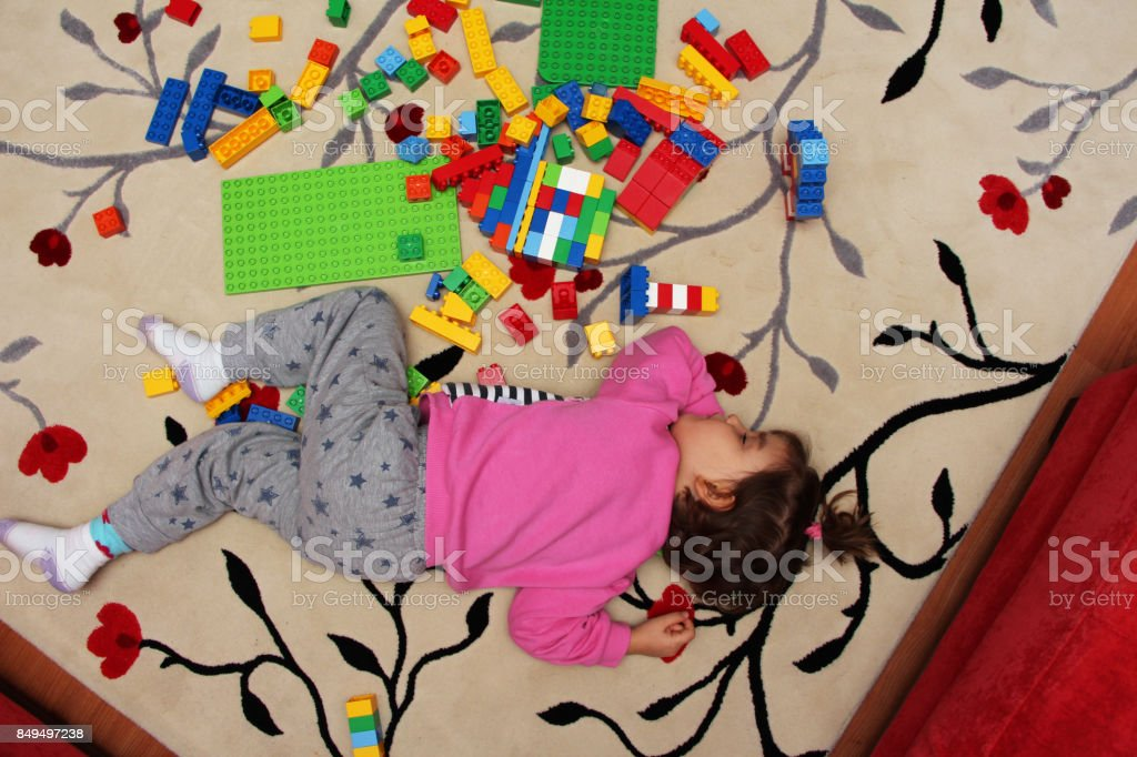 Little child sleeping on carpet with toys stock photo