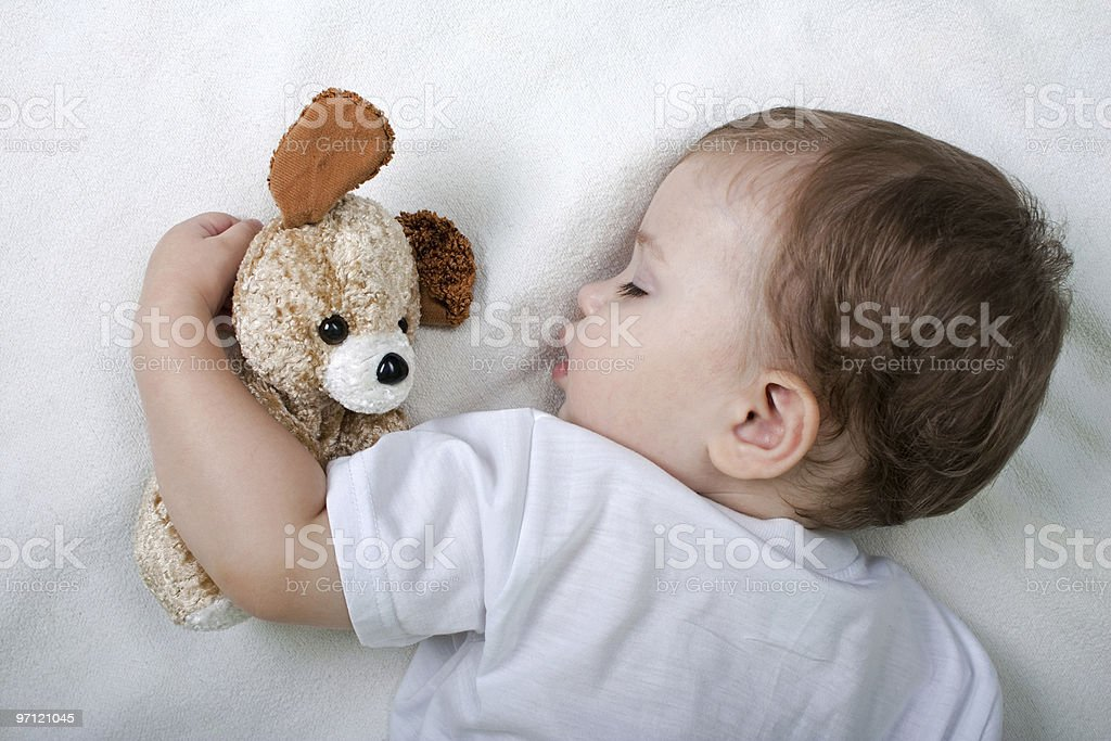 Little child sleeping with teddy bear stock photo