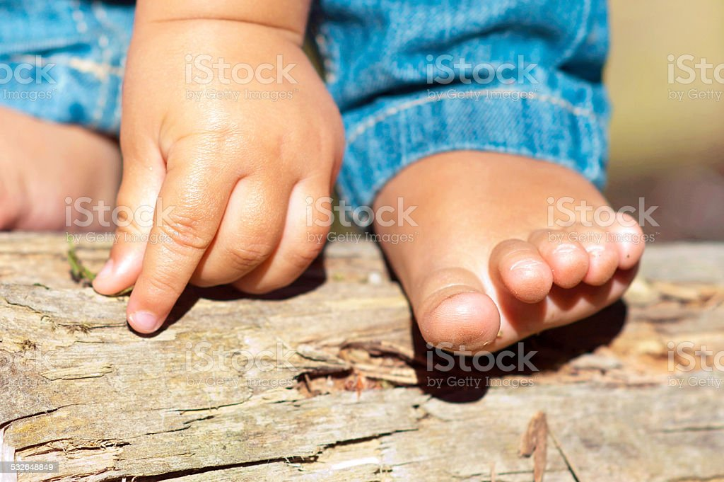 Little child small bare feet and hand in the forest. stok fotoğrafı