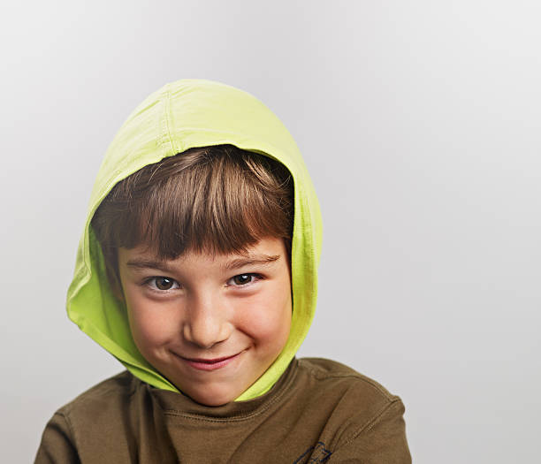 Little child smiling Mischievous child smiling with a hood. smirking stock pictures, royalty-free photos & images