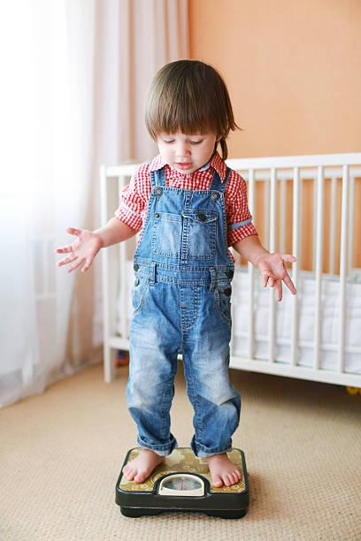 kleines kind auf einer skala - wachstumstabelle baby stock-fotos und bilder