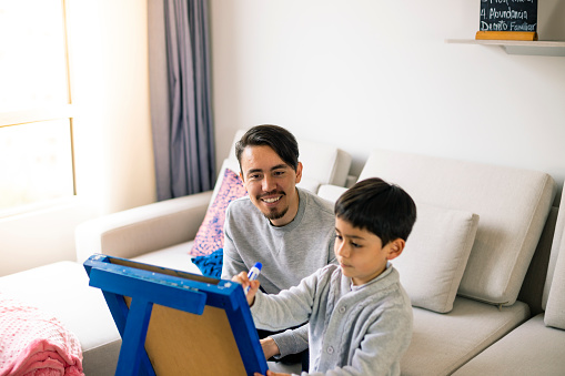 A little child studying at home with a young adult