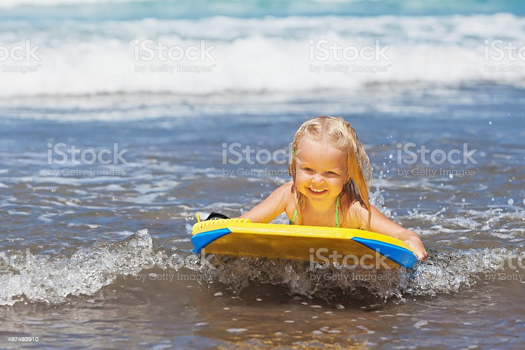 Little child swimming with bodyboard on the sea waves stock photo