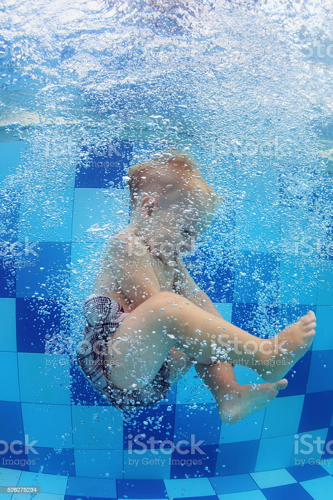 Little child swimming with fun and diving down in pool stock photo