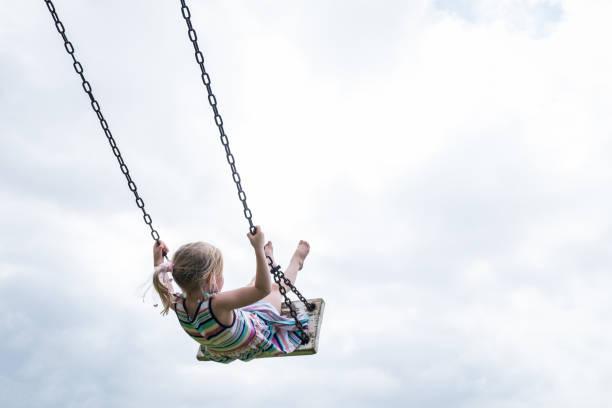 little child swinging on a wooden swing - balouço imagens e fotografias de stock