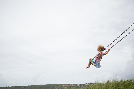 A little girl swings high on a wooden swing on a cloudy day.