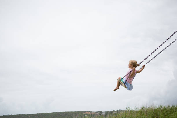 Little child swinging on a wooden swing stock photo