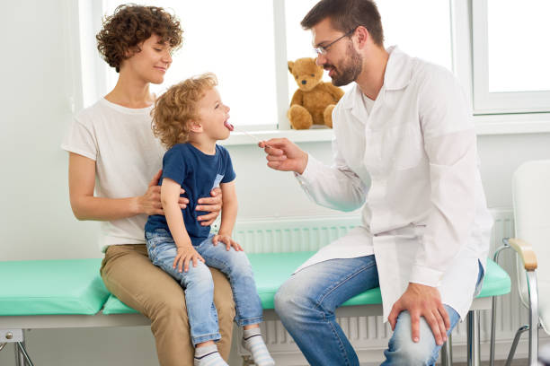 Little Child Visiting Pediatrician Portrait of adorable little boy opening mouth for checkup at doctors office, sitting in mothers lap respiratory disease stock pictures, royalty-free photos & images