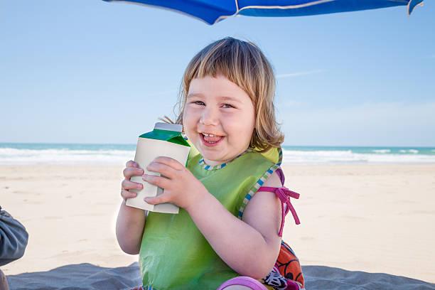 little child with beverage container in hands at beach - kinder verpackung stock-fotos und bilder