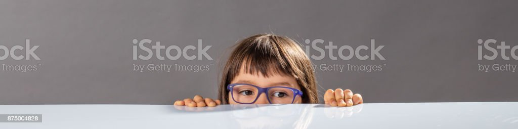 little child with eyeglasses hiding, too small to reach out stock photo