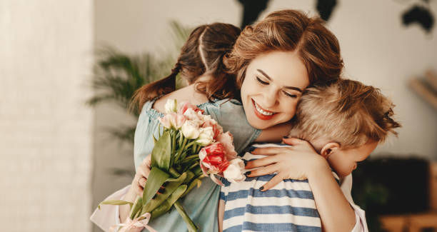 Little children congratulating and hug mother in kitchen Happy Mothers Day! Children boy and girl congratulate smiling mother, hugs her  and give her flowers   bouquet of tulips during holiday celebration in kitchen at home mothers day stock pictures, royalty-free photos & images