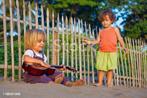 605742160 istock photo Little children have fun on sunset tropical beach. 1199451009