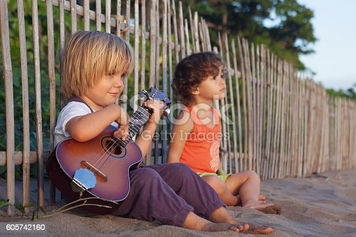 istock Little children have fun on sunset tropical beach. 605742160