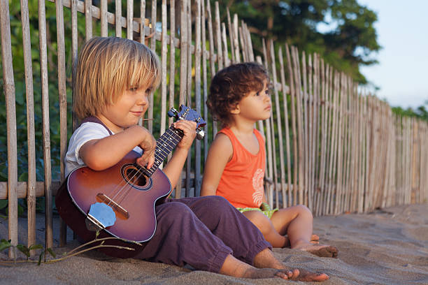 Little children have fun on sunset tropical beach. Little happy boy have fun, play music on Hawaiian guitar ukulele for small baby girl, enjoying sunset ocean beach. Children healthy lifestyle. Travel, family activity on tropical island summer holiday big island hawaii islands stock pictures, royalty-free photos & images