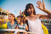 Happy multi-ethnic children having fun with parents on roller coaster amusement park ride in summer