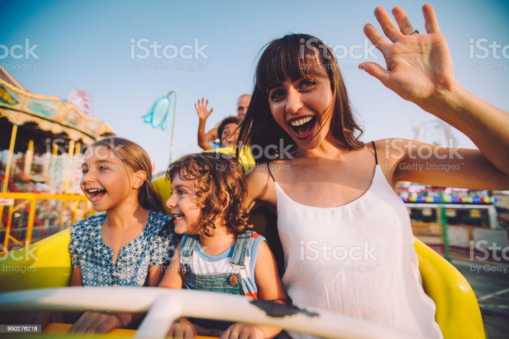 Little children having fun with mother on roller coaster ride stock photo