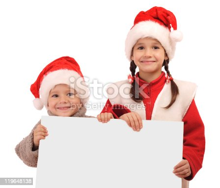 1069359694 istock photo Little children in Christmas hats with an empty banner 119648138