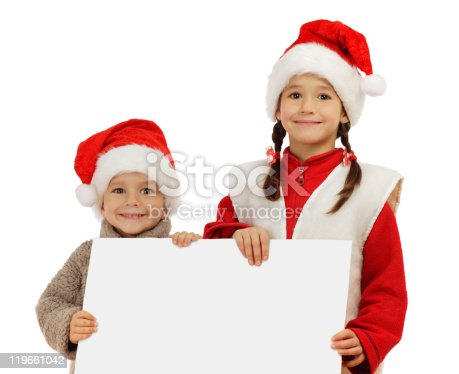 1069359694 istock photo Little children in Christmas hats with an empty banner 119661042