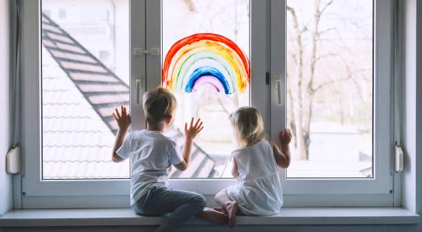 bambini piccoli sullo sfondo della pittura arcobaleno sulla finestra. foto del tempo libero dei bambini a casa. - hand on glass covid foto e immagini stock