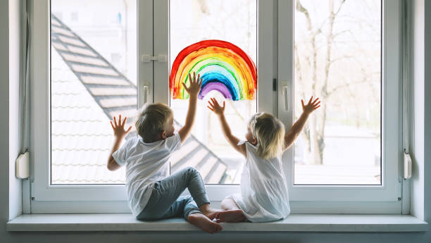Little children on background of painting rainbow on window. Photo of kids leisure at home. stock photo