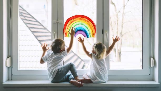 Kleine Kinder auf dem Hintergrund der Malerei Regenbogen auf Fenster. Foto von Kindern Freizeit zu Hause. – Foto
